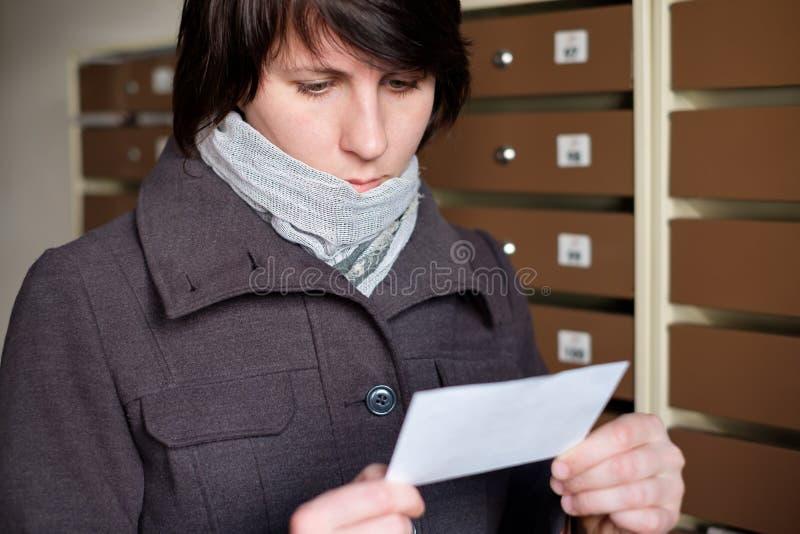 Une fille dans un manteau regardant soigneusement sur la facture reçue par mA image libre de droits