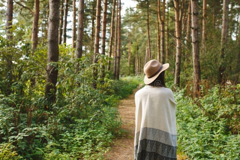 Une fille dans un poncho et un chapeau dans la forêt photographie stock libre de droits