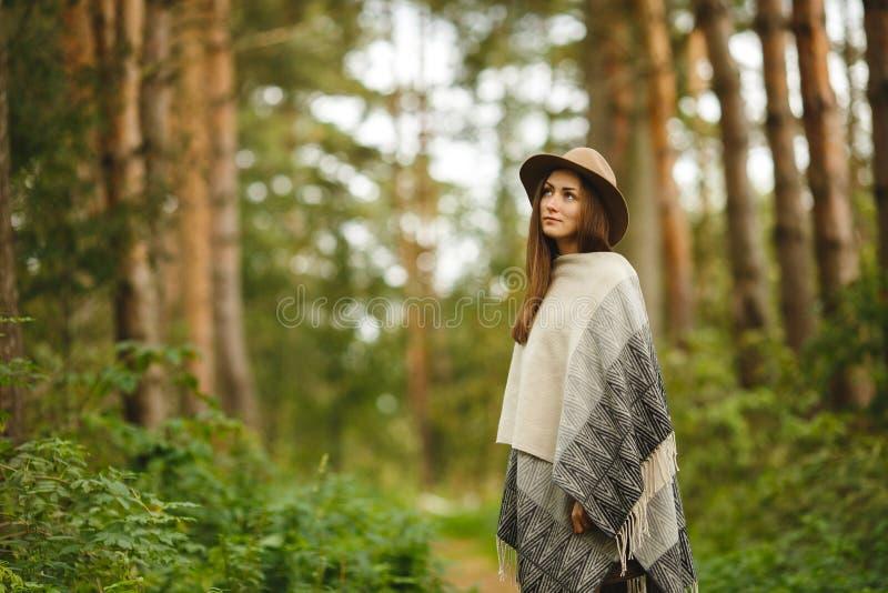 Une fille dans un poncho et un chapeau dans la forêt photos stock