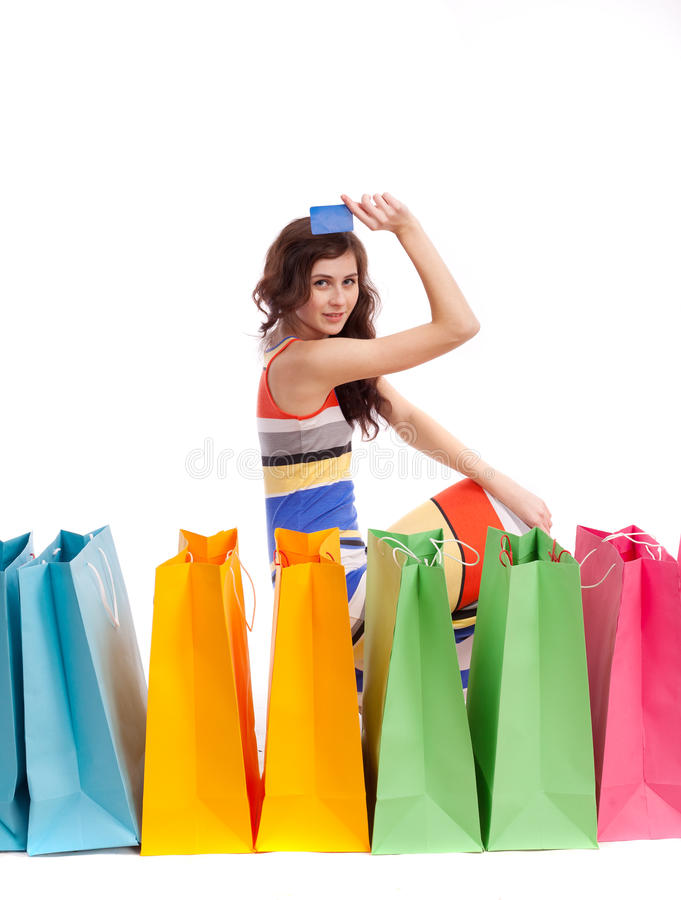 Une fille dans une longue couleur de robe avec des sacs à provisions