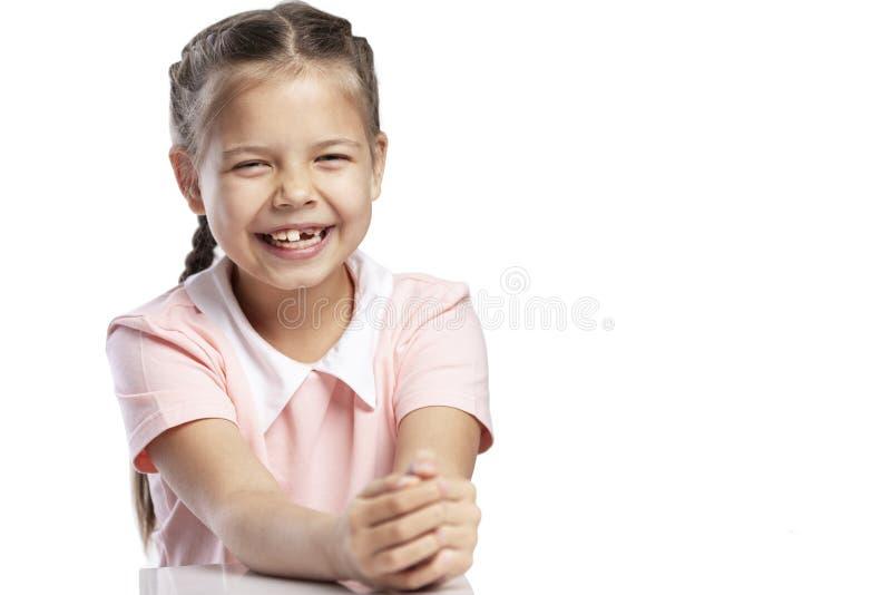 Une fille dans une veste rose d'un âge scolaire sans rires d'une dent avant Plan rapproch? Changement des dents D'isolement au-de photos stock