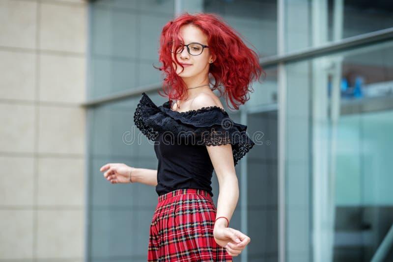 Une fille danse sur la rue Cheveux rouges Concept de mode de vie, urbain, voyage, mode photos stock