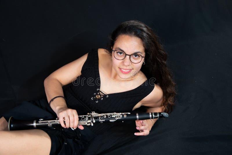 Une fille de brune, avec des verres, rire menteur et juger son instrument de musique de clarinette d'isolement sur un fond noir image libre de droits