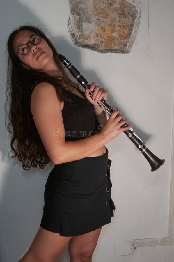 Une fille de brune avec des verres, tout en jouant son instrument de musique de clarinette, d'isolement sur un fond blanc image stock