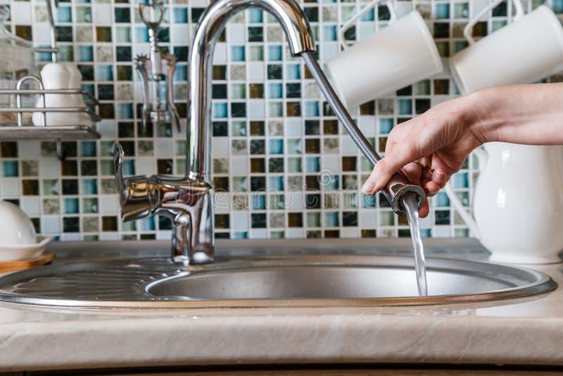 Une fille de femme au foyer utilise un robinet de cuisine avec un tuyau pour les plats de lavage photo stock