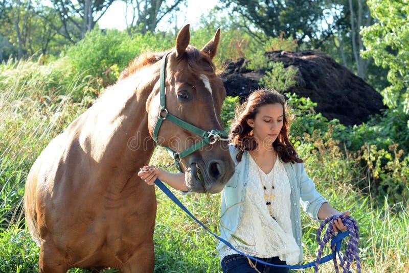 Une fille de l'adolescence marche avec son cheval photo libre de droits