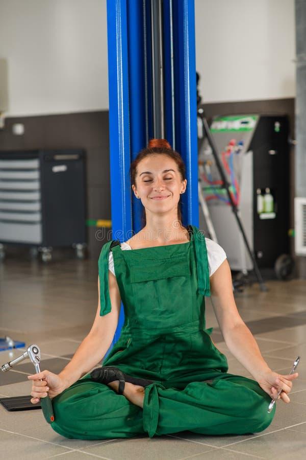 Une fille de mécanicien médite près d'un ascenseur de voiture photo libre de droits