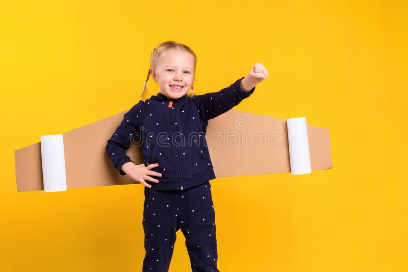 Une fille de petit enfant utilise les ailes de vol faites maison de carton, feignant pour être un pilote pour un métier, imaginat photographie stock