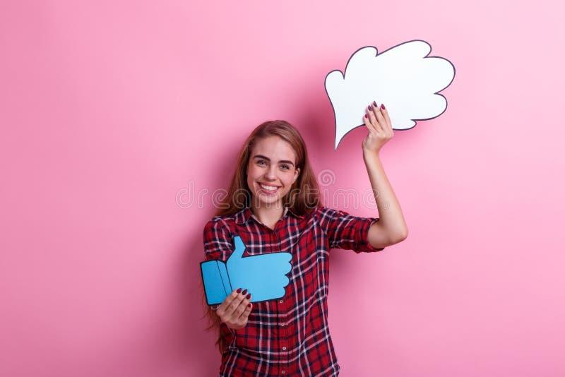 Une fille de sourire, les prises une image de papier de pensée ou l'idée et des pouces lèvent le signe Sur un fond rose photographie stock