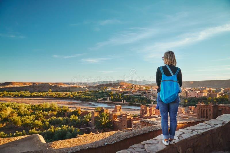 Une fille de touristes regardant la rivière et le village d'oasis d'Ait Ben Haddou images libres de droits