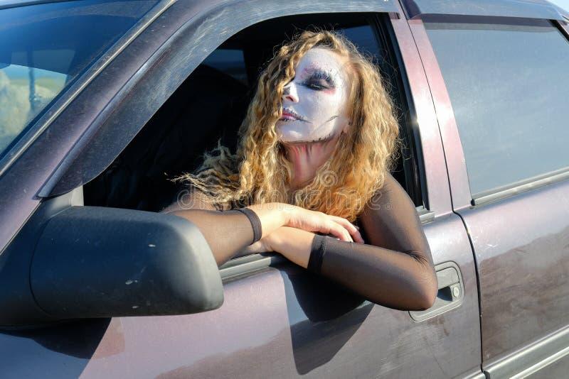 Une fille de zombi avec des yeux au beurre noir et une bouche ensanglantée dans la voiture image libre de droits