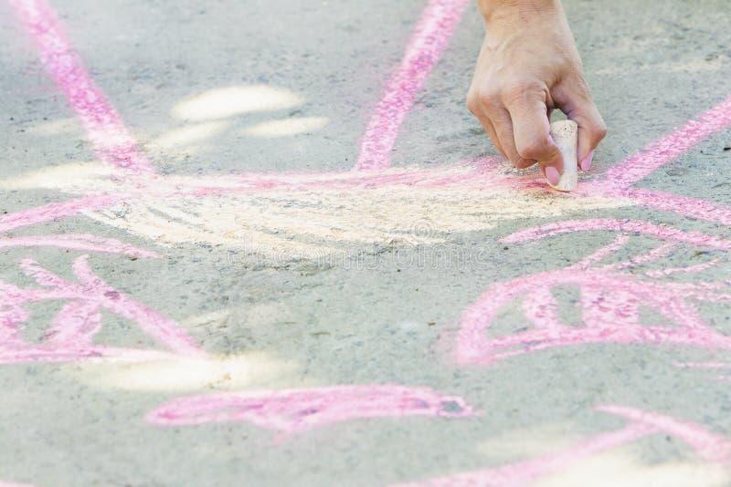 Une fille dessine avec des crayons sur la route photographie stock libre de droits