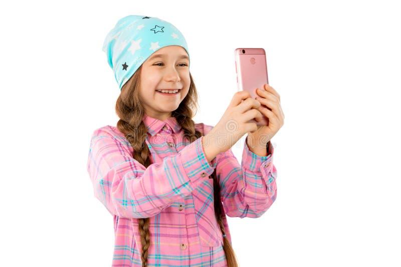 Une fille douce tient un téléphone intelligent dans ses mains et sourires D'isolement sur un fond blanc image libre de droits
