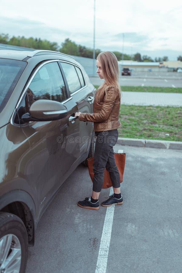 Une fille en veste et jeans ouvre la porte de la voiture dans un parking près d'un centre commercial. Activation de l'alarme. VUS images libres de droits