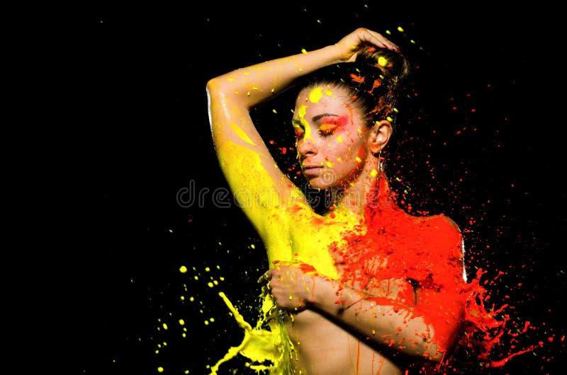 Une fille est baignée en peinture jaune d'un côté et peinture orange de l'autre Avec une main, la fille clôture son sein, et t image libre de droits