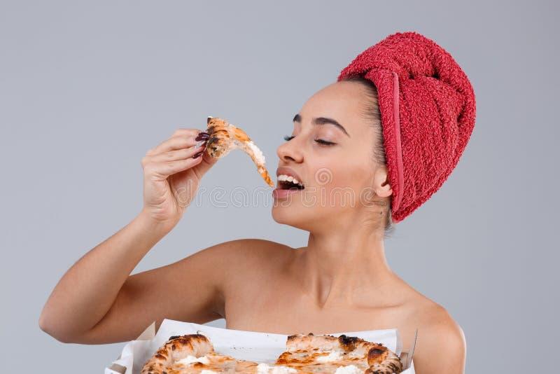 Une fille est enveloppée dans une serviette sur le chef, mangeant un morceau de pizza sur un fond gris photographie stock