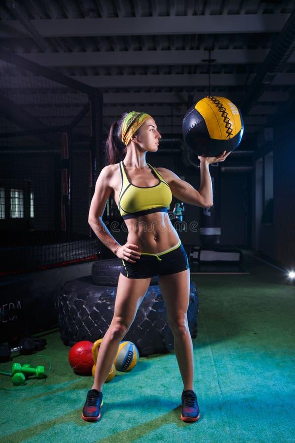 Une fille forte dans un gymnase s'exerce avec la boule Santé, concept de sport images stock