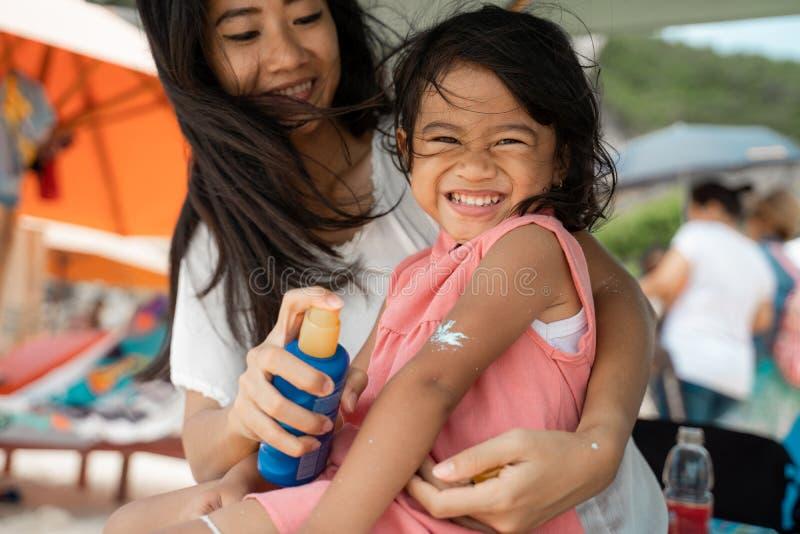 Une fille heureuse a amusé le regard à la caméra quand sa mère donnent un sunblock photo stock