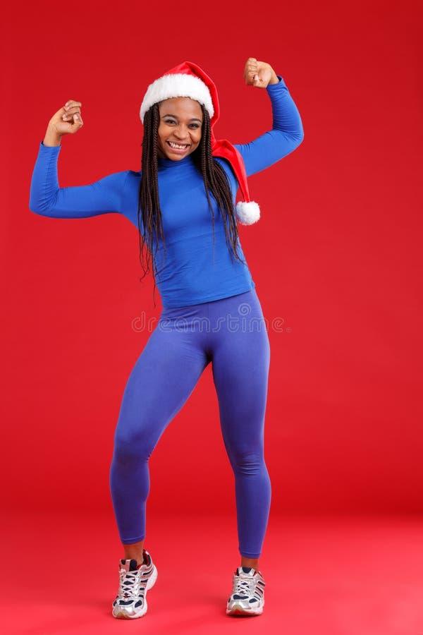 Une fille heureuse d'afro-américain dans le chapeau de Noël, danse gaiement soulevant ses mains photo stock