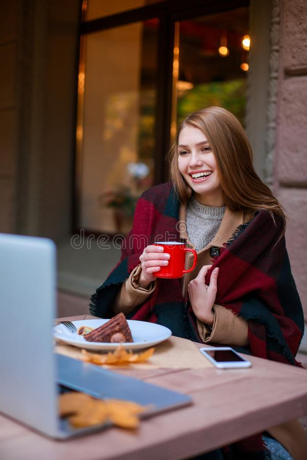 Une fille heureuse, enveloppée dans une couverture, s'assied dans un café parlant à quelqu'un sur un ordinateur portable, mangean images stock