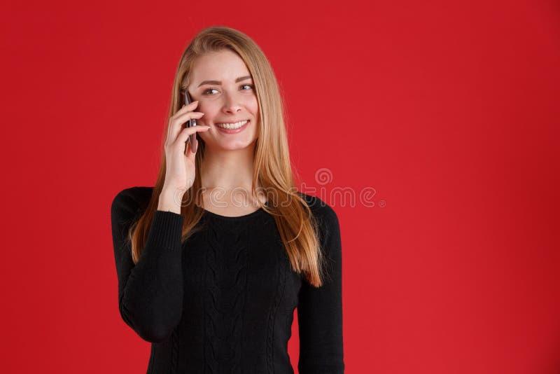 Une fille heureuse parlant sur le téléphone portable, regardant parti et le sourire photographie stock