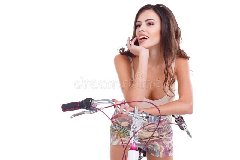 Une fille heureuse, s'assied sur une bicyclette, tient la main près du visage et rit D'isolement sur le fond blanc photo libre de droits