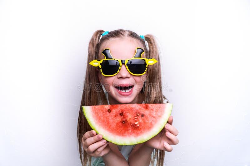 Une fille heureuse, un enfant dans des lunettes de soleil jaunes, mange une pastèque rouge mûre Portrait photo stock
