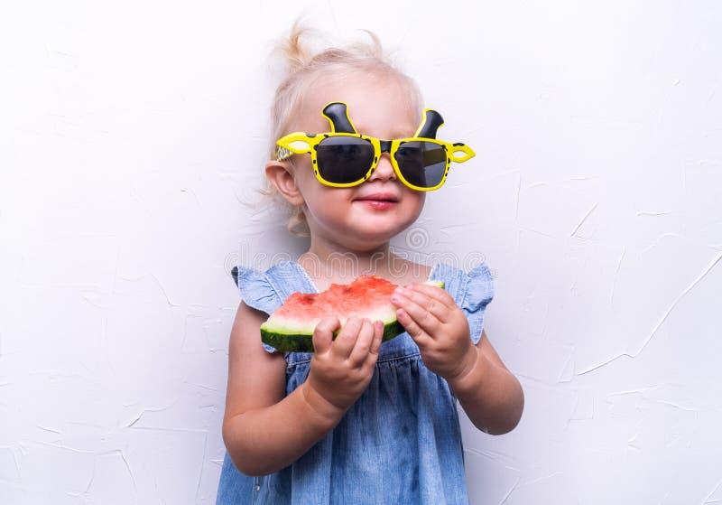 Une fille heureuse, un enfant dans des lunettes de soleil jaunes, mange une pastèque rouge mûre Portrait image stock