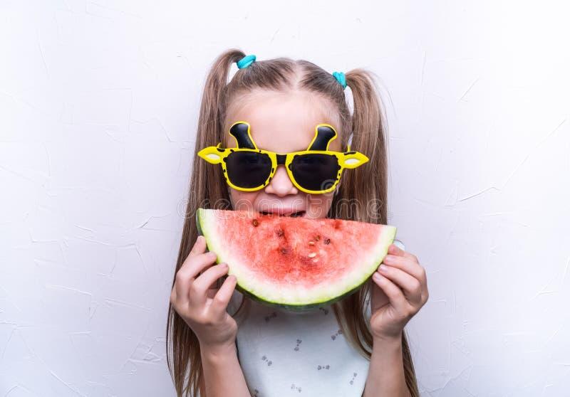 Une fille heureuse, un enfant dans des lunettes de soleil jaunes, mange une past?que rouge m?re Portrait photo stock