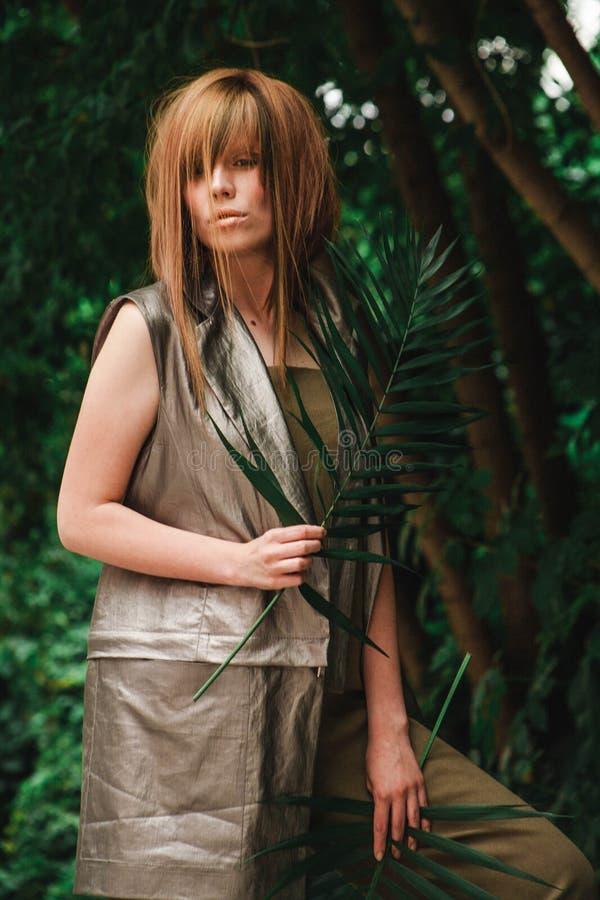 Une fille incroyablement belle dans une forêt avec une fougère photographie stock