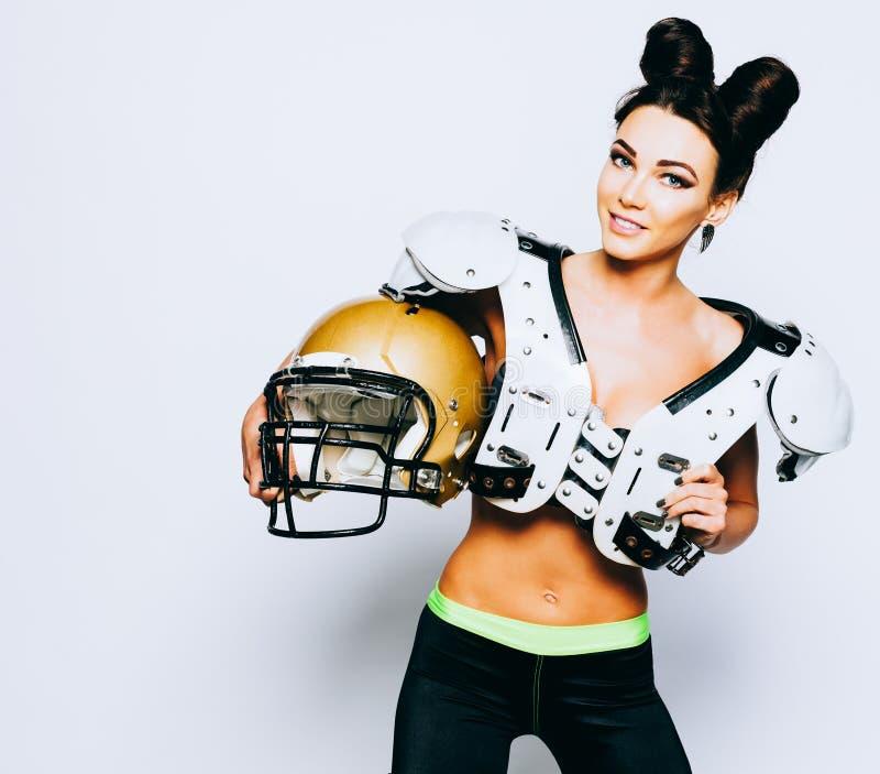 Une fille incroyablement belle et sportive de brune dans shoulderpads et un casque de football américain démontrant la stupéfacti photos libres de droits