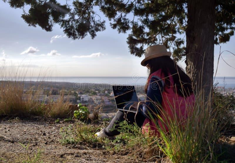 Une fille indépendante assise avec un ordinateur portable sur l'herbe sous un arbre, avec en toile de fond une belle vue sur la v images stock