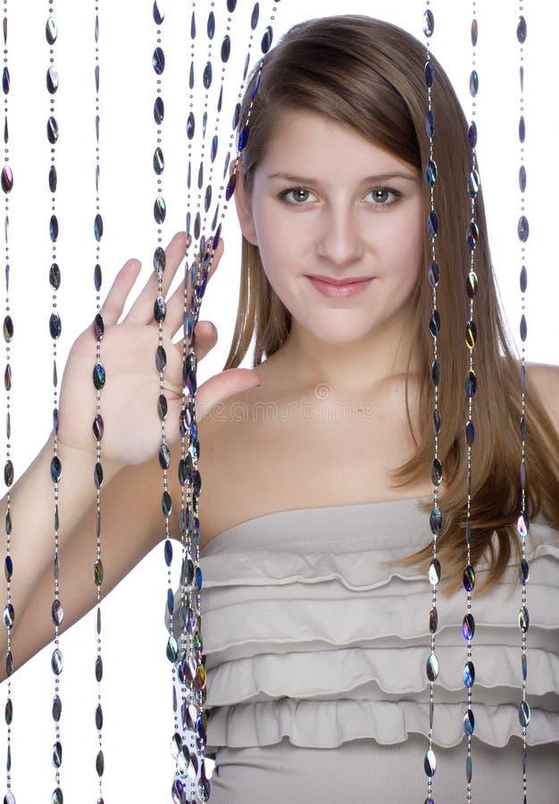 Une fille jette un coup d'oeil du rideau images libres de droits