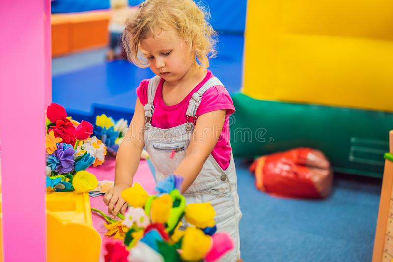Une fille joue dans un fleuriste, choisit des fleurs image libre de droits