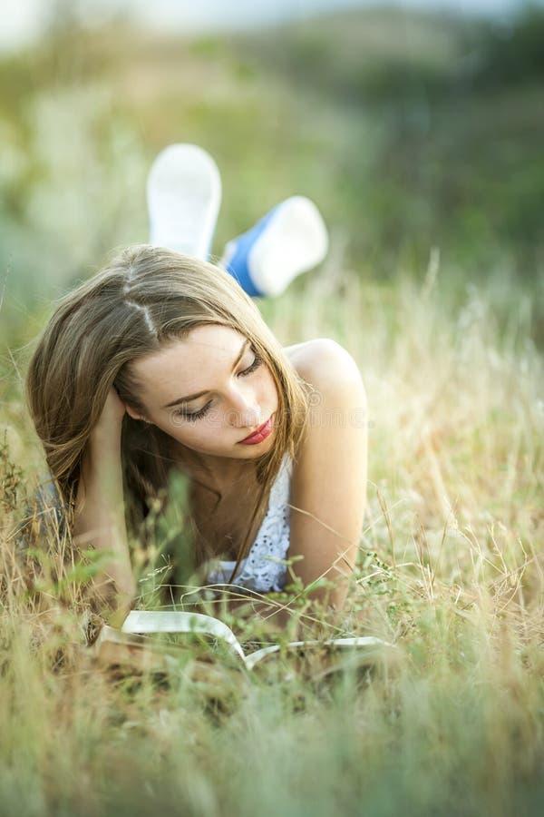 Une fille lisant un livre dehors photos libres de droits