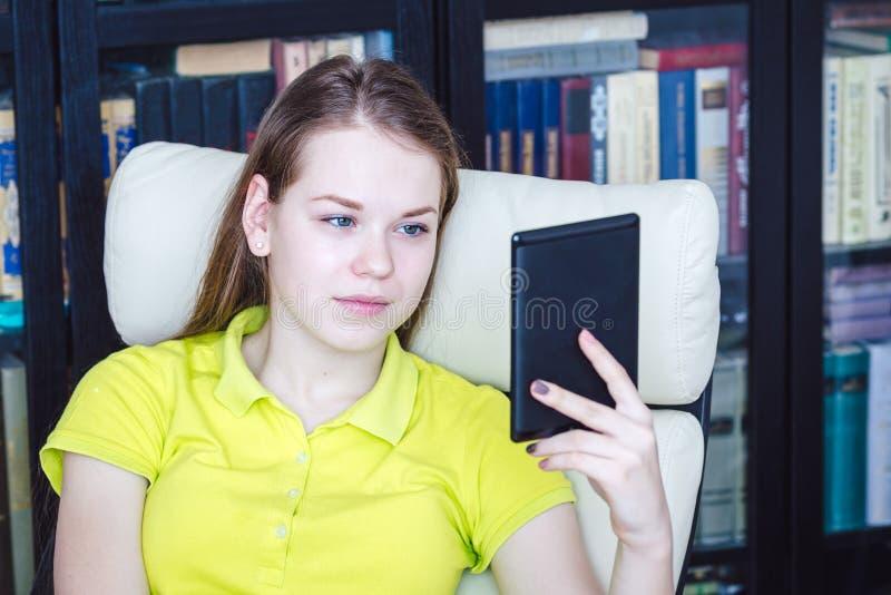 Une fille lit l'eBook photo stock