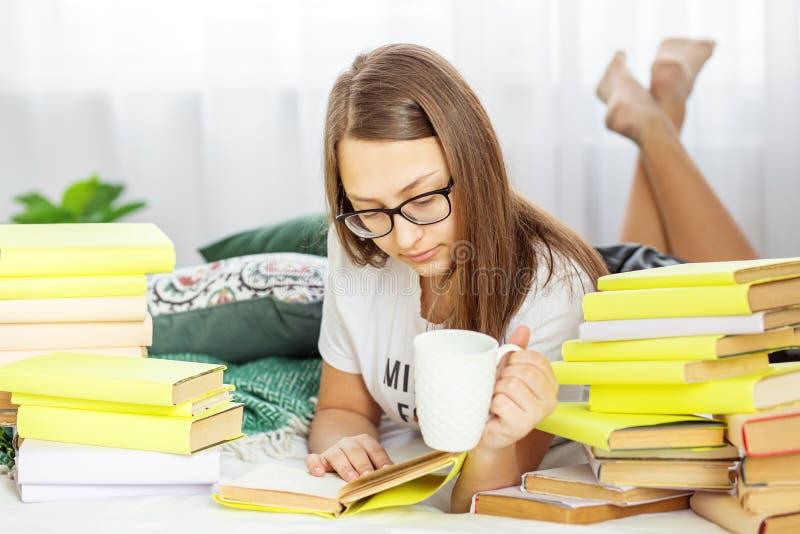 Une fille lit un livre avec des verres Un étudiant boit du café Concept d'éducation, passe-temps et étude et jour de livre du mon images libres de droits