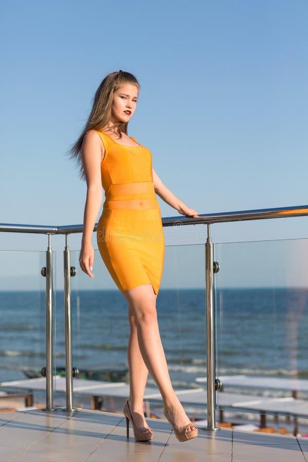 Une fille magnifique sur une terrasse sur le secteur d'été du ` s d'hôtel Une dame fascinante dans une robe orange avec des talon images libres de droits