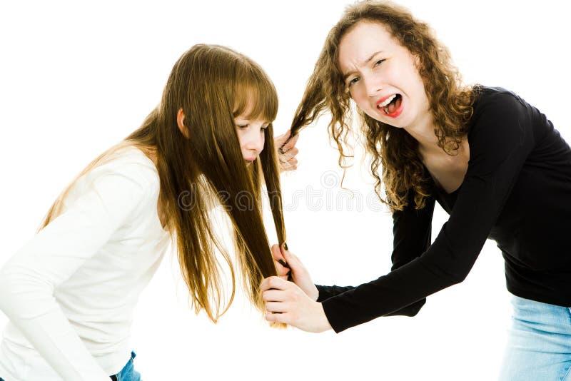 Une fille maltraitant autre en tirant ses poils - l'amour de la soeur photos libres de droits