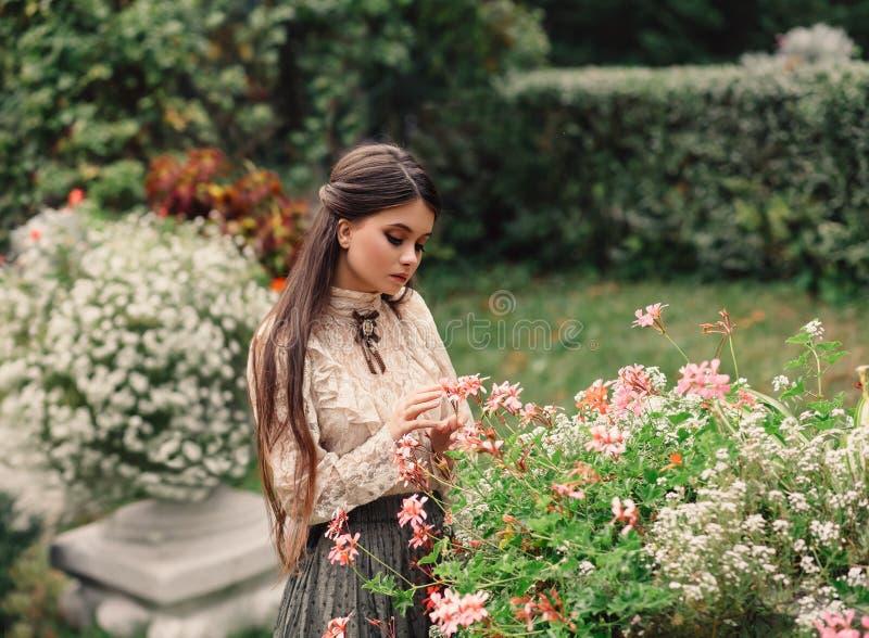 Une fille marche dans un jardin fleurissant, elle a un chemisier de vintage avec un arc, longs cheveux de châtaigne elle s'occupe photographie stock libre de droits