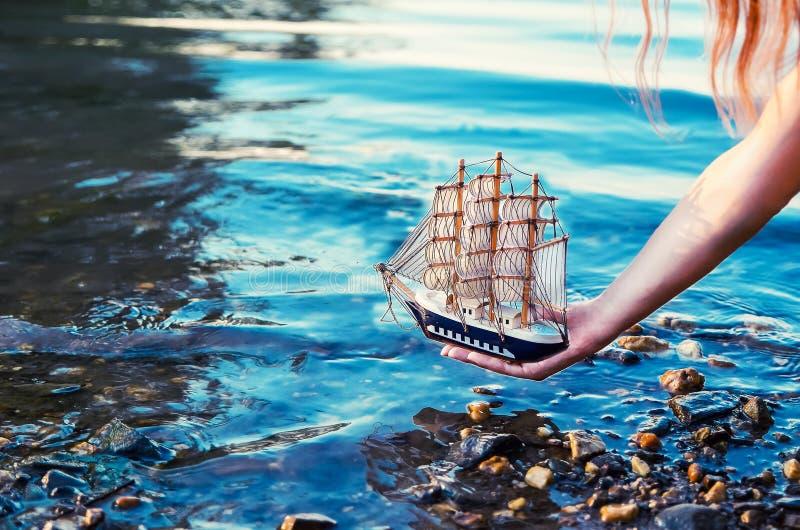 Une fille met à l'eau un bateau de navigation dans l'eau du rivage Lumière du soleil modifiée la tonalité photographie stock