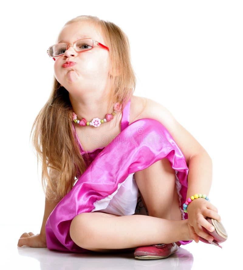 Une fille mignonne souffle ses joues d'isolement photographie stock libre de droits