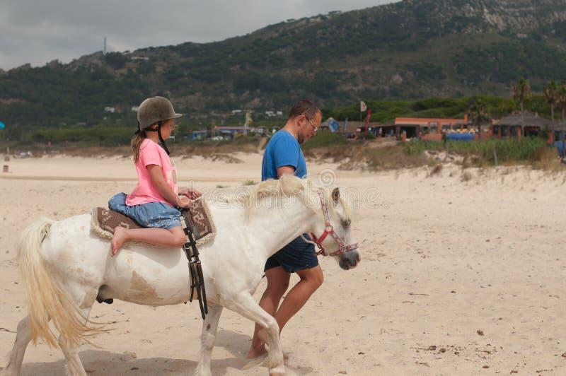 Une fille montant un cheval avec un entraîneur images stock