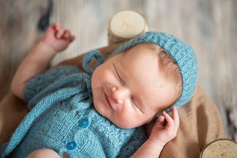 Une fille nouveau-née de sommeil, dans un lit en bois fait en bouleau Le sourire dans un bleu a tricoté le costume et le chapeau images stock