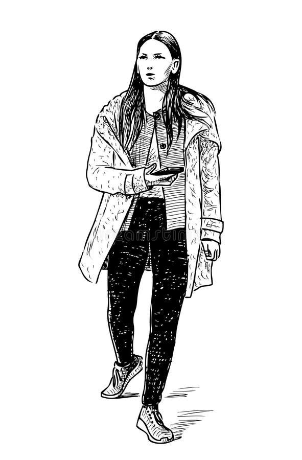 Une fille occasionnelle avec un téléphone portable descend la rue illustration libre de droits