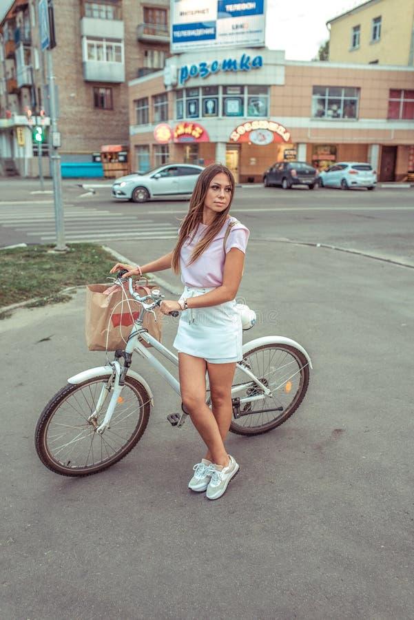 Une fille pendant l'été dans des supports de ville avec une bicyclette, attendant l'occasion de traverser la route par la route photos libres de droits