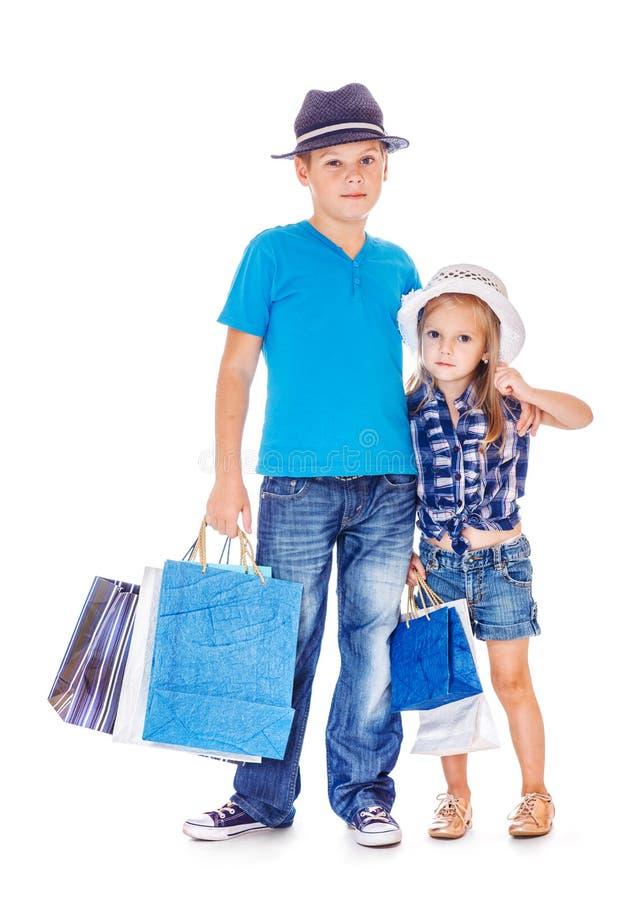 Garçon et fille avec des sacs en papier de client images libres de droits