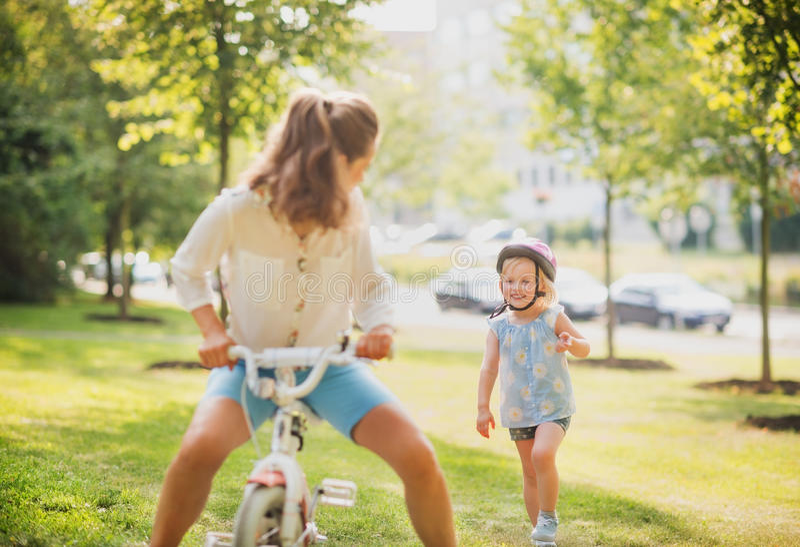 Une fille portant un casque chasse après sa mère photo stock