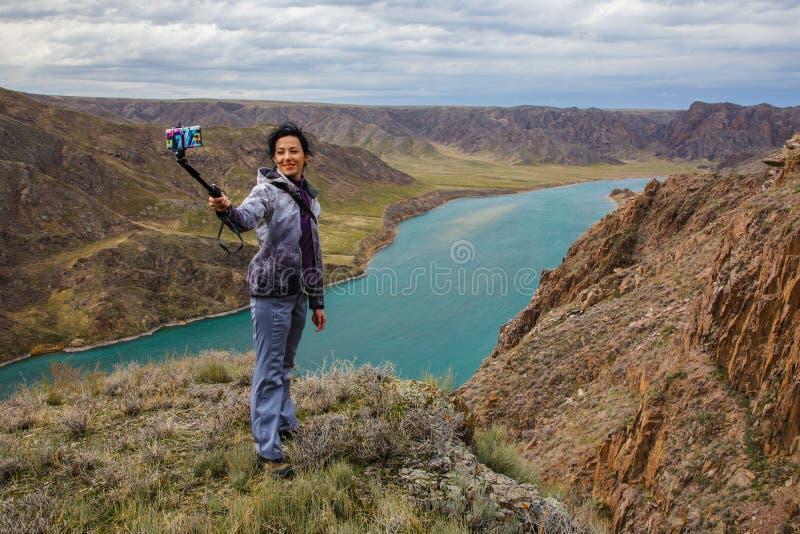 Une fille prend un selfie sur un smartphone sur le fond de la rivière photo stock
