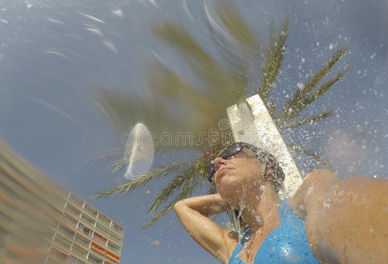 Une fille prend une douche sur la plage de magaluf dans Majorca images stock